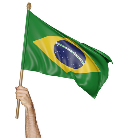 Hand proudly waving the national flag of Brazil