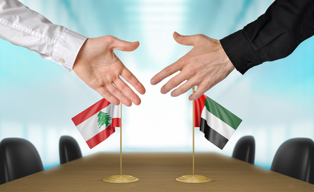 estar de acuerdo: Líbano y Emiratos Árabes Unidos diplomáticos dándose la mano para acordar acuerdo Foto de archivo
