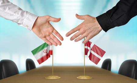 estar de acuerdo: Irán y Dinamarca diplomáticos dándose la mano para acordar acuerdo