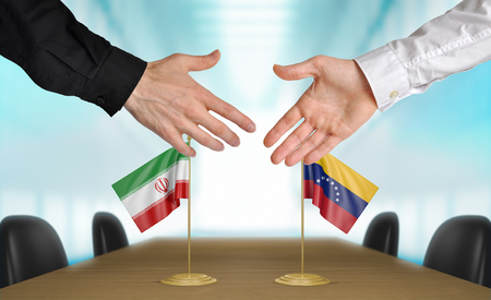diplomats: Iran and Venezuela diplomats shaking hands to agree deal