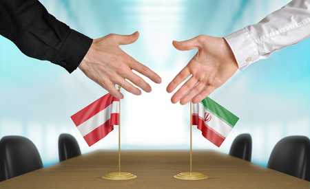 union flag: Austria and Iran diplomats shaking hands to agree deal