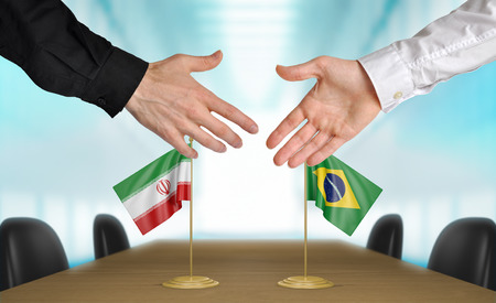 diplomats: Iran and Brazil diplomats shaking hands to agree deal