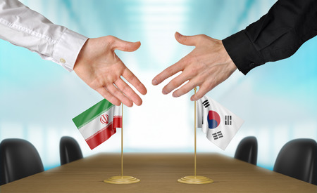korea flag: Iran and South Korea diplomats shaking hands to agree deal Stock Photo