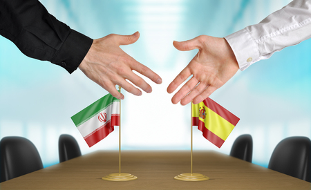 diplomats: Iran and Spain diplomats shaking hands to agree deal
