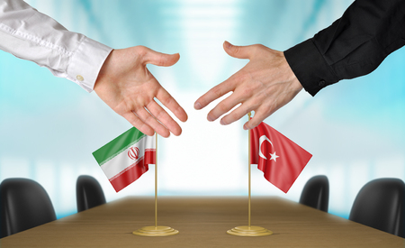 diplomats: Iran and Turkey diplomats shaking hands to agree deal