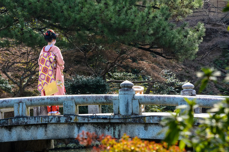 Young geisha woman on a bridge in Maruyama Park, Kyoto during spring Stockfoto