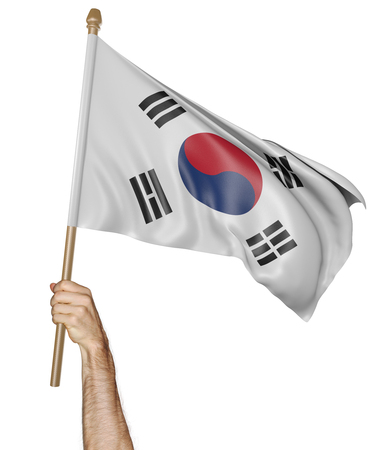 Hand proudly waving the national flag of South Korea