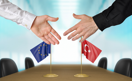 EU: European Union and Turkey diplomats shaking hands to agree deal