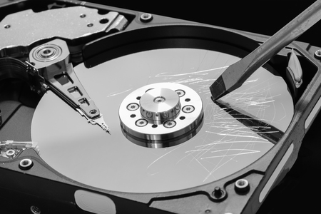 disks: Screwdriver destroying a hard disk drive platter to erase the data Stock Photo