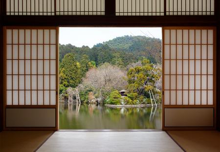 Uitzicht op een mooie oosterse vijver, gezien door open Japanse schuifdeuren