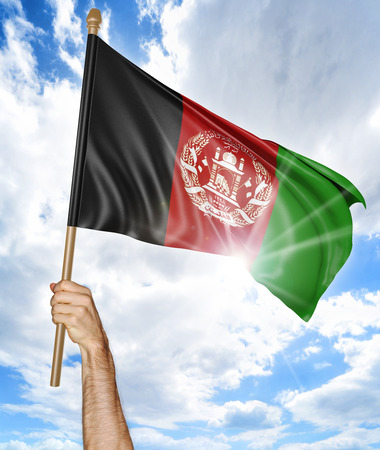 afghan flag: Persons hand holding the Afghan national flag and waving it in the sky, 3D rendering Stock Photo