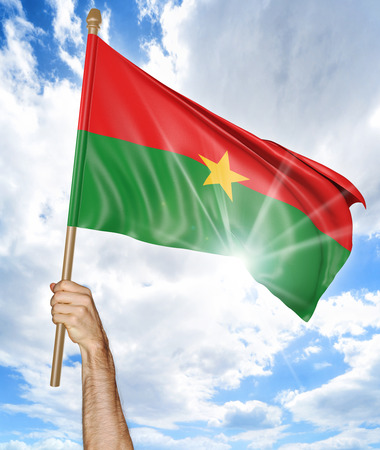 raising: Persons hand holding the Burkina Faso national flag and waving it in the sky, part 3D rendering