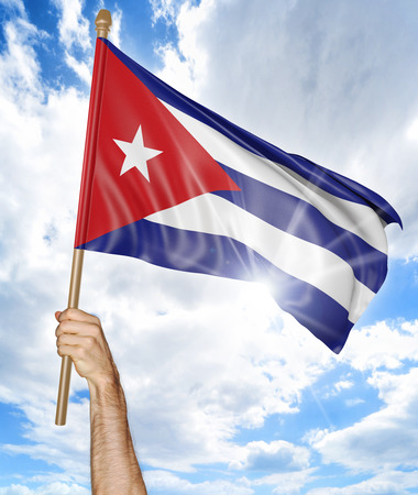 raising: Persons hand holding the Cuban national flag and waving it in the sky, part 3D rendering