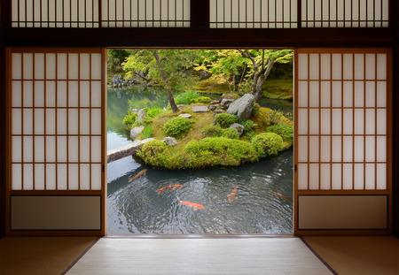 カラフルなオレンジ色鯉が泳いでいる水の中で日本のドアと魚のいる池をスライディング