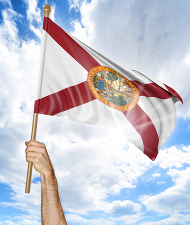 floridian: Persons hand holding the Florida state flag and waving it in the sky, 3D rendering