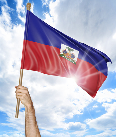 haitian: Persons hand holding the Haitian national flag and waving it in the sky, 3D rendering