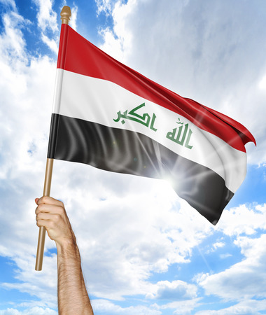iraqi: Persons hand holding the Iraqi national flag and waving it in the sky, 3D rendering Stock Photo