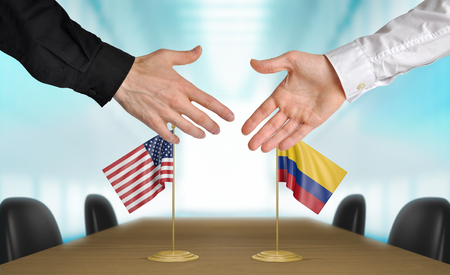 foreign trade: United States and Colombia diplomats shaking hands to agree deal, part 3D rendering Stock Photo