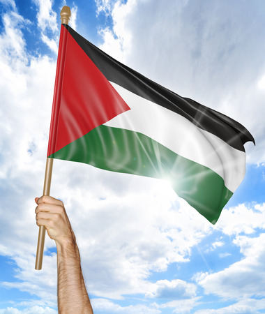 palestinian: Persons hand holding the Palestinian national flag and waving it in the sky, 3D rendering Stock Photo