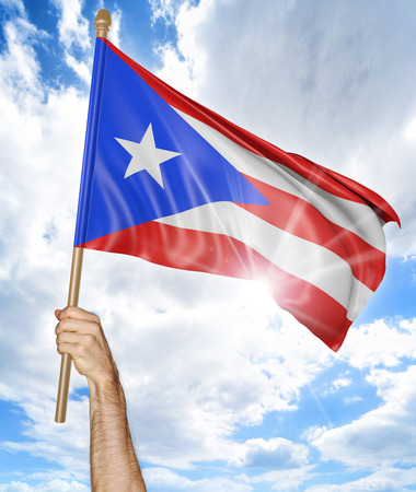 Persons hand holding the Puerto Rican national flag and waving it in the sky, 3D rendering