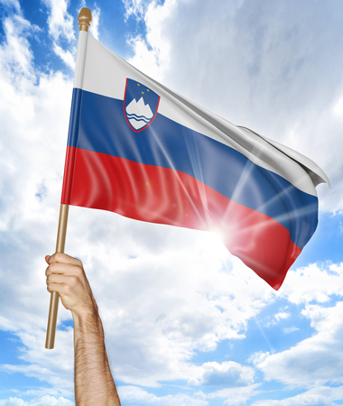 activism: Persons hand holding the Slovenian national flag and waving it in the sky, 3D rendering