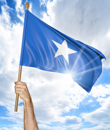 somalian culture: Persons hand holding the Somalian national flag and waving it in the sky, 3D rendering