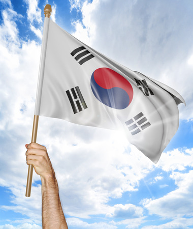 Person's hand holding the South Korean national flag and waving it in the sky, 3D rendering Foto de archivo