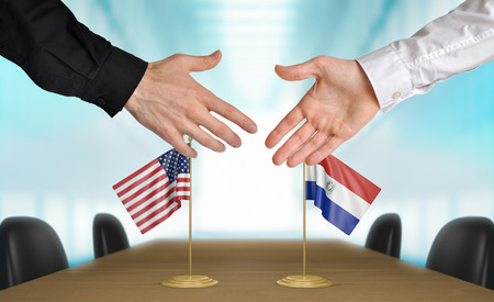 agree: United States and Paraguay diplomats shaking hands to agree deal, part 3D rendering Foto de archivo