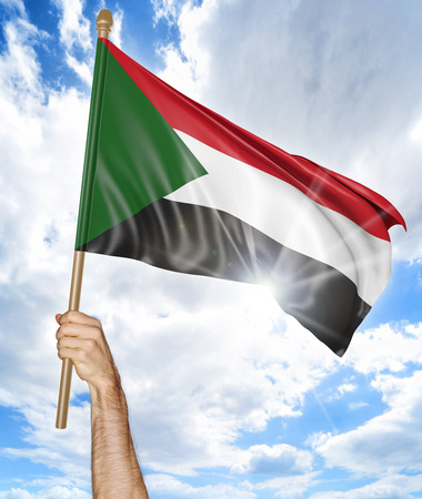 Persons hand holding the Sudanese national flag and waving it in the sky, 3D rendering