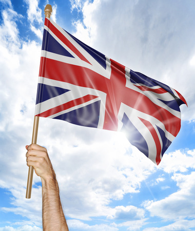 uk: Persons hand holding the British national flag and waving it in the sky, 3D rendering