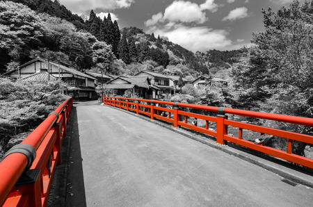 Black and white photo of a small Japanese village with selective color on the red bridge