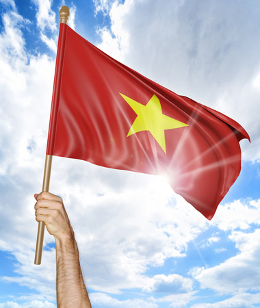 Persons hand holding the Vietnamese national flag and waving it in the sky, 3D rendering