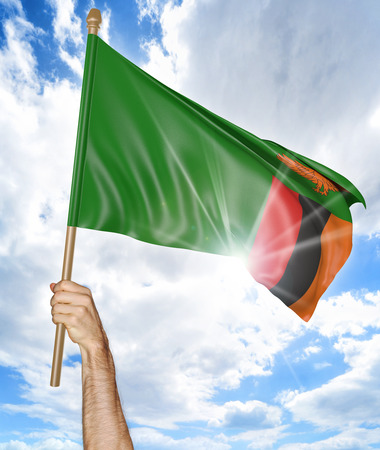 Persons hand holding the Zambian national flag and waving it in the sky, 3D rendering