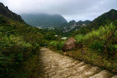 jiufen: Hiking path leading into the mountains from Jiufen, Taiwan with Mount Keelung shrouded in clouds in the background