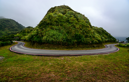 potentially: Potentially dangerous hairpin curve on a mountain road along the coast of Jiufen, Taiwan Stock Photo