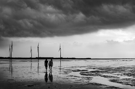 romantic love: Black and white of romantic couple in love and holding hands as they face a big storm together