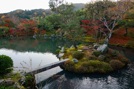 Beautiful autumn lake with a bridge to a small island and red maples growing on the banks