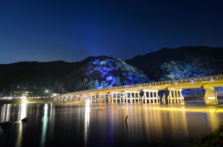 Long exposure of night illuminations on the Togetsu Bridge and mountains during Arashiyama Hanatouro festival in Kyoto