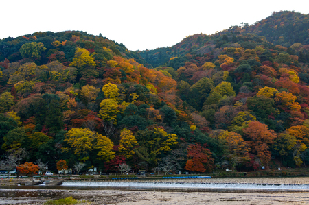 Katsura River and Mount Arashi in full autumn color in the Arashiyama district of Kyoto, Japan