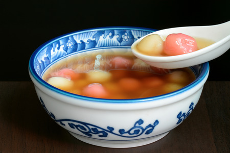 tang: Bowl of sweet Chinese tangyuan dessert being eaten with a spoon Stock Photo