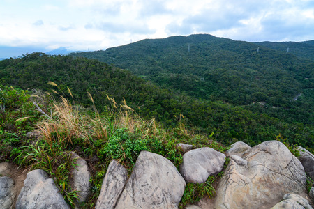mian: Diverse Taiwan landscape of huge rocks, tall grass, low hills, and forested mountains along the Jin Mian trail in Neihu