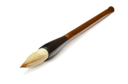 Traditional Chinese calligraphy brush lying on a white background