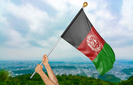 Young mans hands proudly waving the Afghanistan national flag in the sky, part 3D rendering Stock Photo