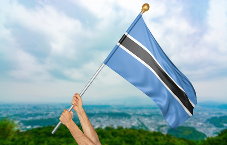 botswanan: Young mans hands proudly waving the Botswana national flag in the sky, part 3D rendering