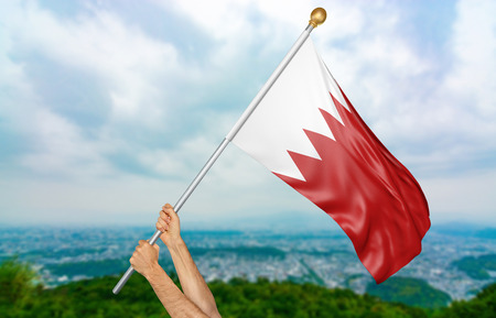 Young mans hands proudly waving the Bahrain national flag in the sky, part 3D rendering