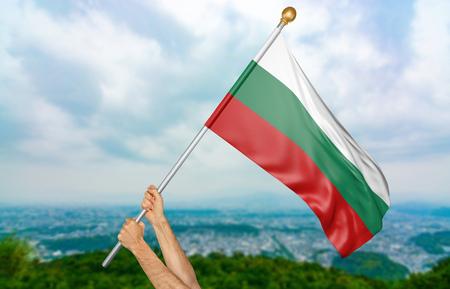Les mains d'un jeune homme agitant fièrement le drapeau national de Bulgarie dans le ciel, rendu 3D