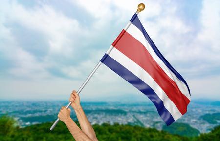 Manos del joven que agitan orgulloso la bandera nacional de Costa Rica en el cielo, parte que rinde 3D Foto de archivo