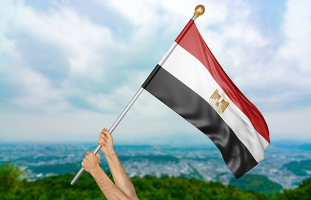 egypt revolution: Young mans hands proudly waving the Egypt national flag in the sky, part 3D rendering
