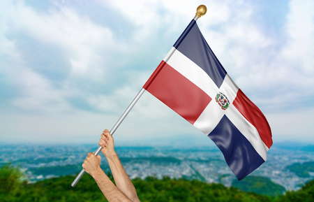 Young mans hands proudly waving the Dominican Republic national flag in the sky, part 3D rendering