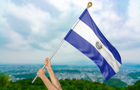 Young mans hands proudly waving the El Salvador national flag in the sky, part 3D rendering Stock Photo